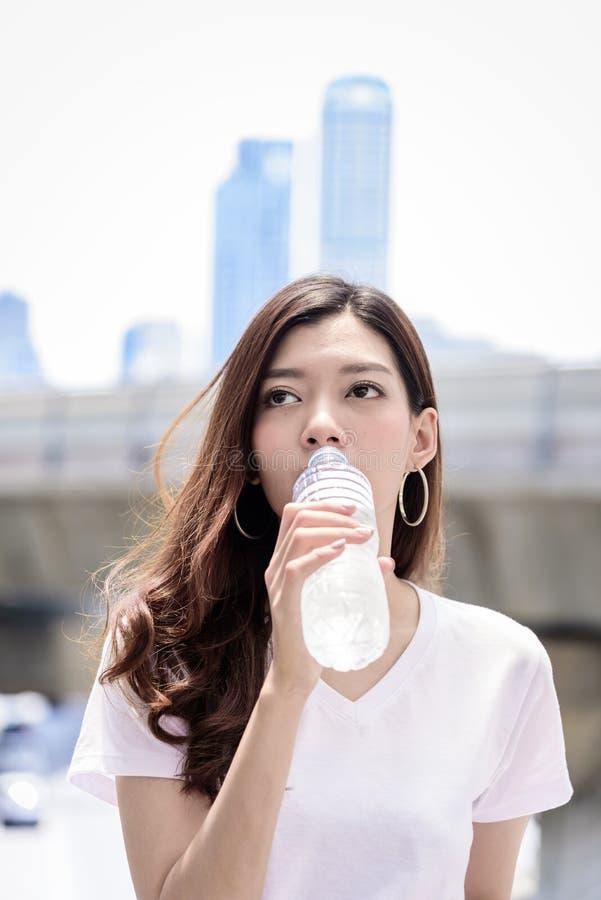 La bella donna asiatica ha acqua che beve con il fondo della città dentro fotografia stock