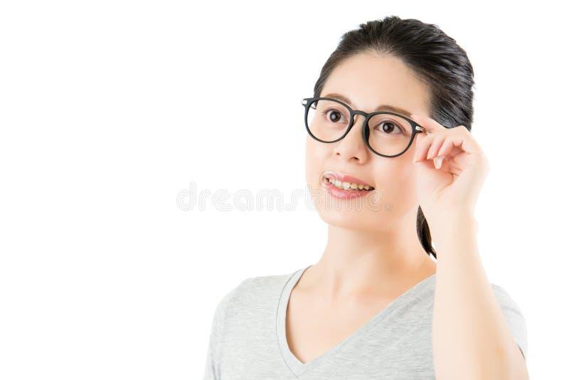 La bella donna asiatica prova sopra i nuovi vetri di modo di occhiali fotografia stock