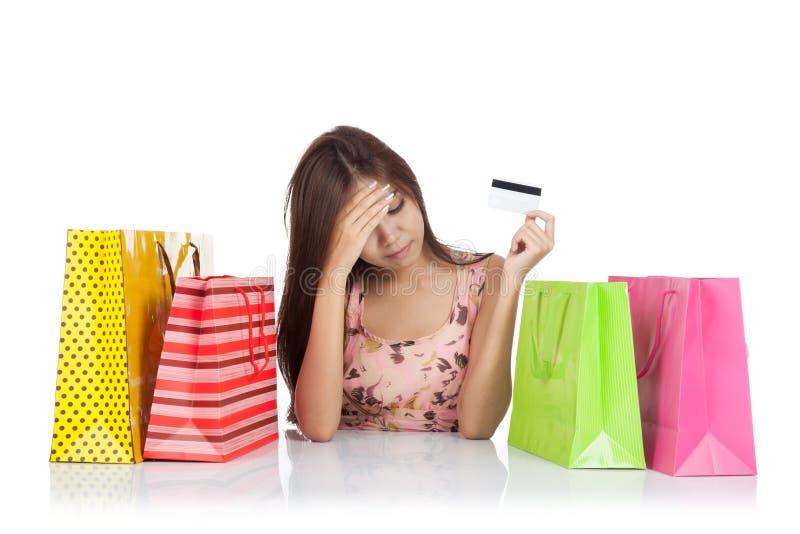 La bella donna asiatica si è alimentata su con una carta di credito e un sacchetto della spesa immagini stock