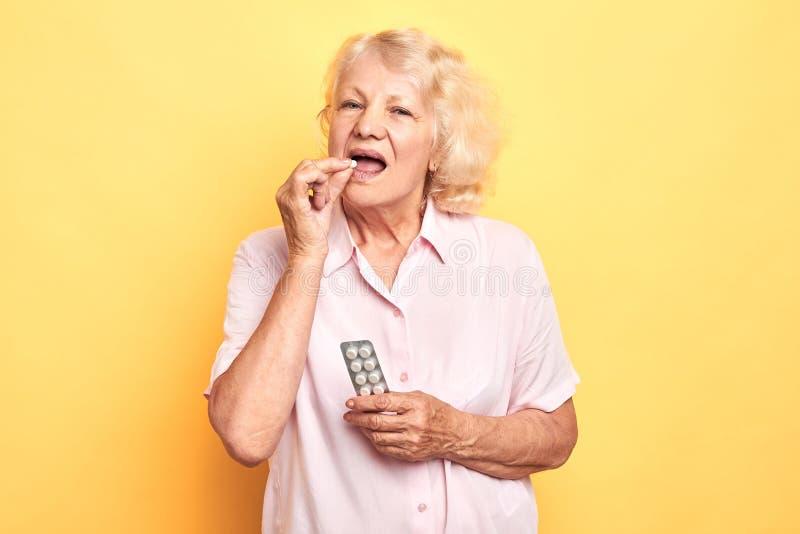 La bella donna bionda anziana prende una pillola immagine stock