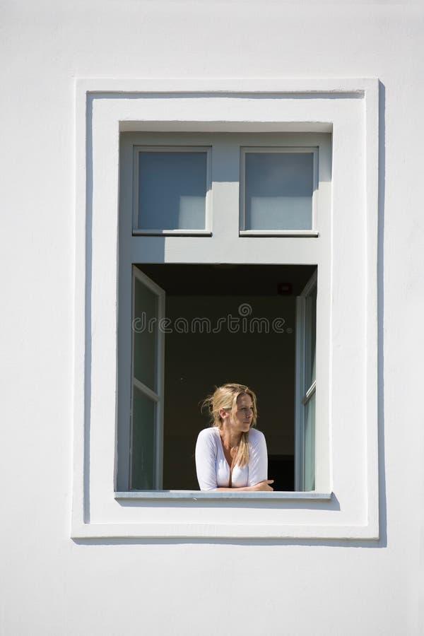 La bella donna bionda guarda fuori dalla finestra aperta, dalla parete bianca e dalla struttura della finestra bianca fotografie stock