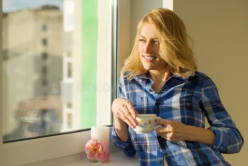 La bella donna bionda matura guarda fuori la finestra nell'appartamento, beve il caffè immagine stock