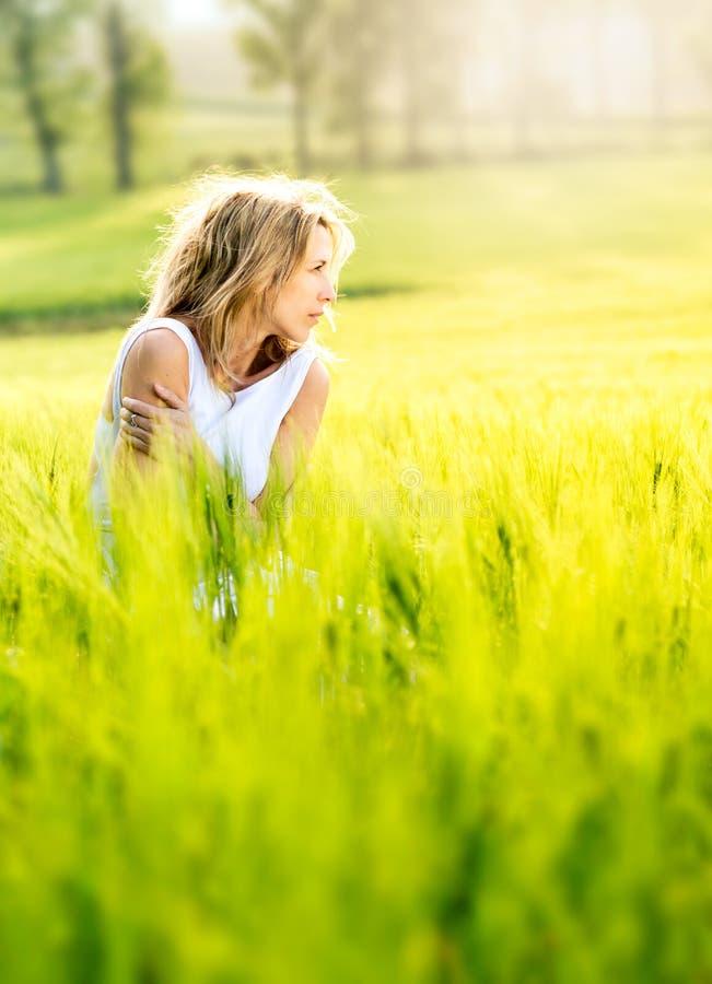 La bella donna bionda si siede in mezzo ad un campo immagini stock libere da diritti