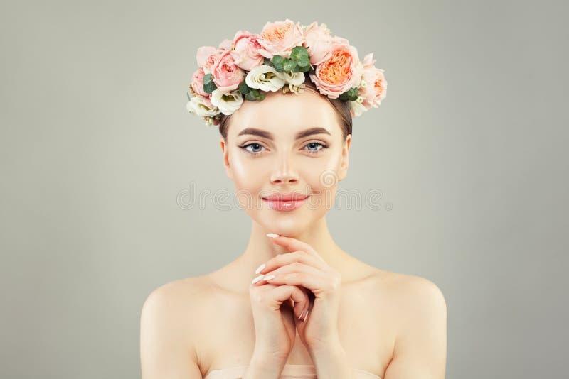 La bella donna in buona salute con chiara pelle e l'offerta sono aumentato fiori Skincare e concetto facciale di trattamento fotografia stock