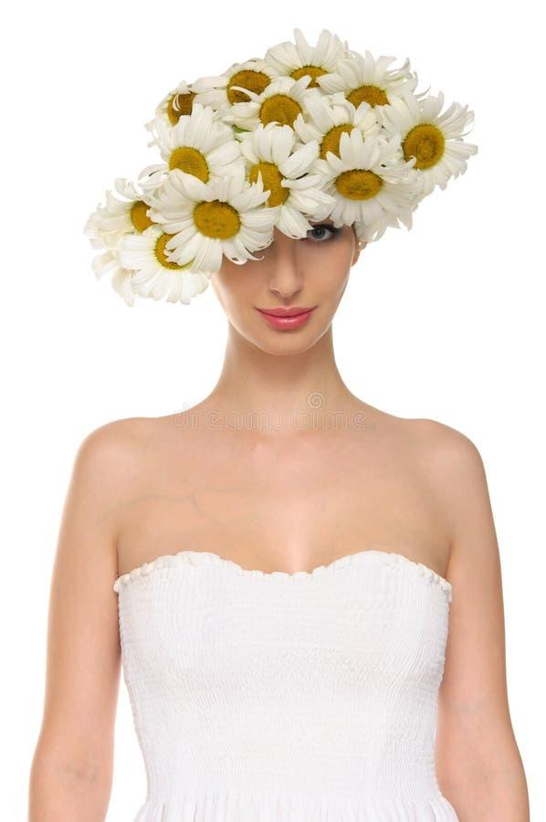 La bella donna in cappello delle margherite ed il bianco si vestono immagine stock