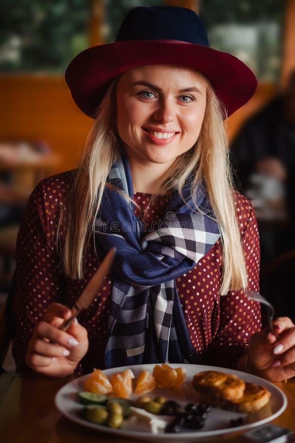La bella donna in cappello ed il vestito hanno assaggiare la prima colazione fotografie stock