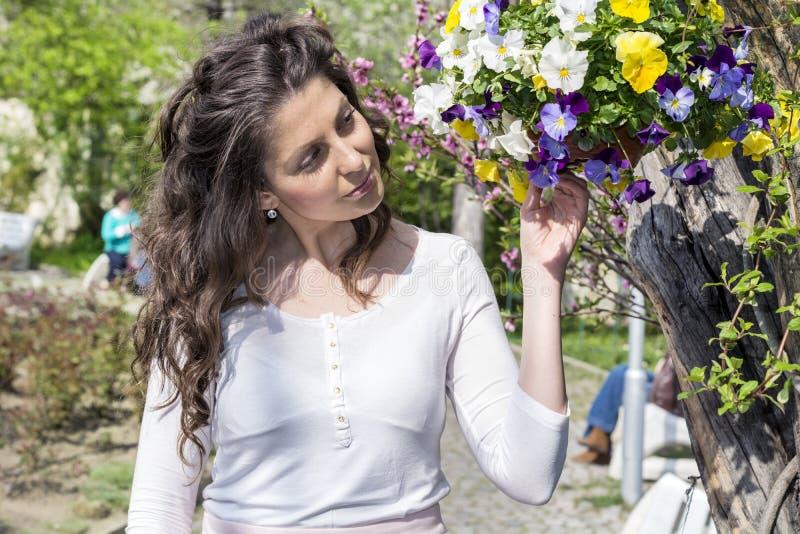 La bella donna castana che odora la molla fresca fiorisce in un giardino di fioritura immagine stock libera da diritti