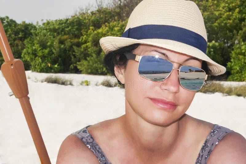 La bella donna castana incantata guarda il mare nelle isole tropicali delle Maldive immagini stock