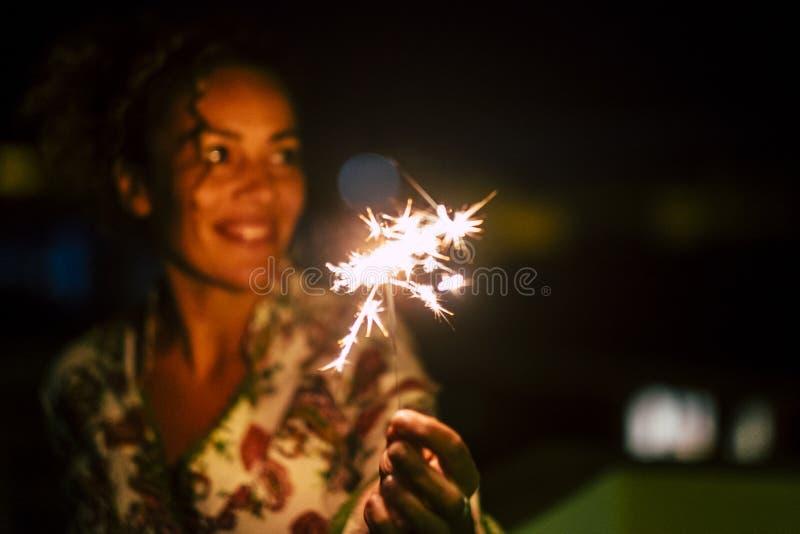 La bella donna caucasica celebrare con le scintille accende di notte - fuoco su fuoco - il concetto dei fuochi d'artificio per la fotografia stock libera da diritti