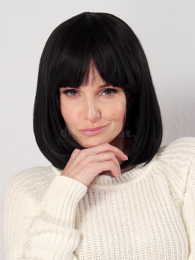 La bella donna caucasica sta posando contro un bakcground bianco immagine stock