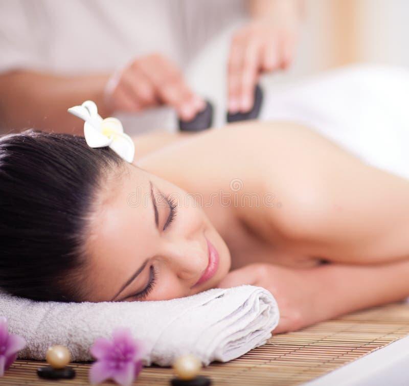 La bella donna che ha un benessere indietro massaggia con le pietre calde immagini stock