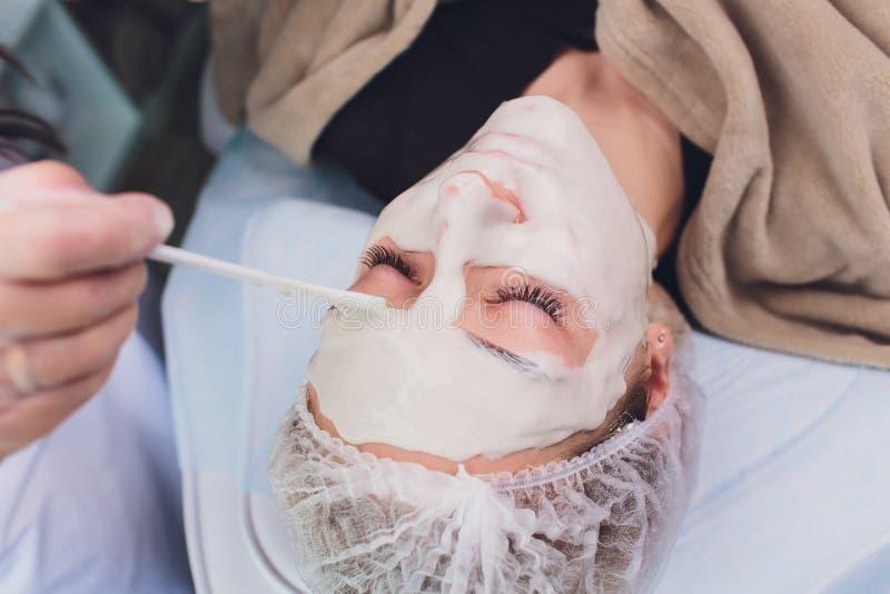 La bella donna che ha un cosmetico facciale sfrega il trattamento dal dermatologo professionista alla stazione termale di benesse fotografie stock libere da diritti