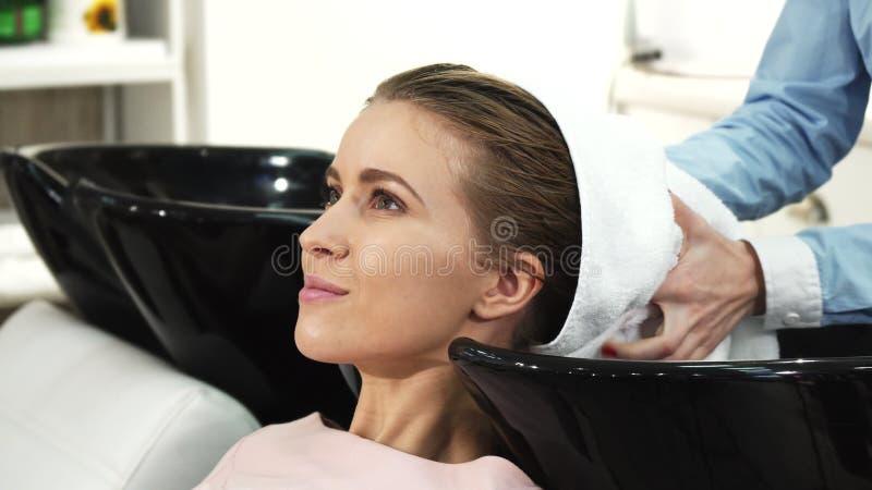 La bella donna che sorride ottenendole i capelli si è asciugata da un parrucchiere professionista fotografia stock libera da diritti