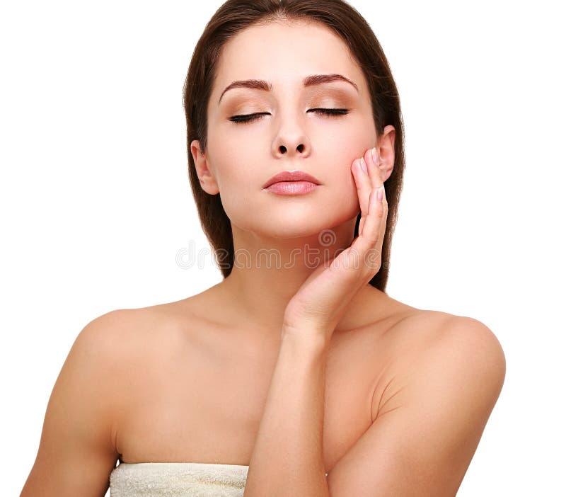 La bella donna commovente le passa la pelle pulita sana del fronte immagini stock