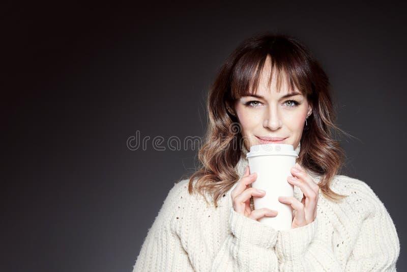 La bella donna con capelli lunghi che indossano le tenute rosse del maglione e del cappello mostra la tazza di caffè eliminabile  fotografie stock