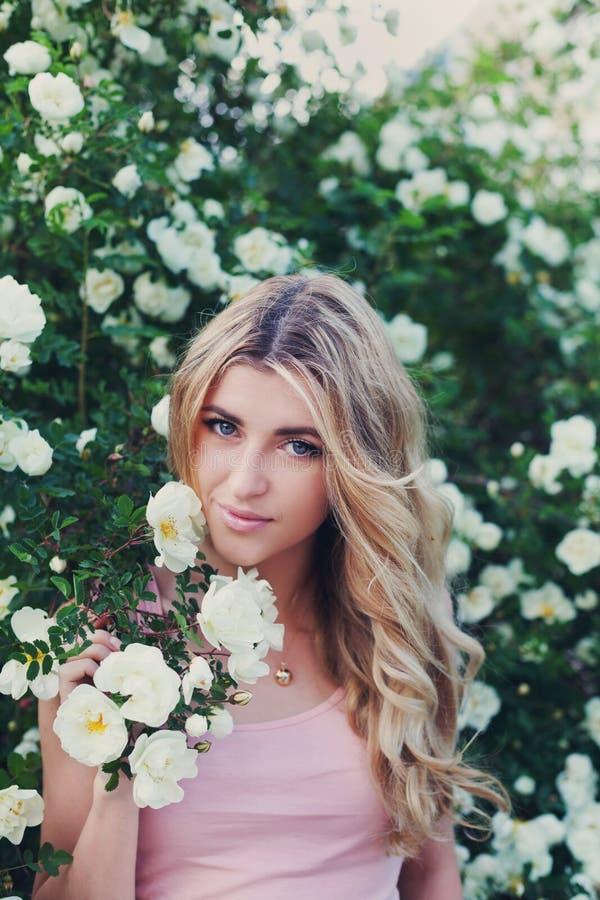 La bella donna con capelli ricci lunghi odora le rose bianche all'aperto, ritratto del primo piano del fronte sensuale della raga fotografia stock libera da diritti
