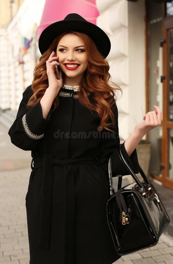 La bella donna con capelli ricci scuri ed il sorriso affascinante, indossa i vestiti eleganti immagine stock