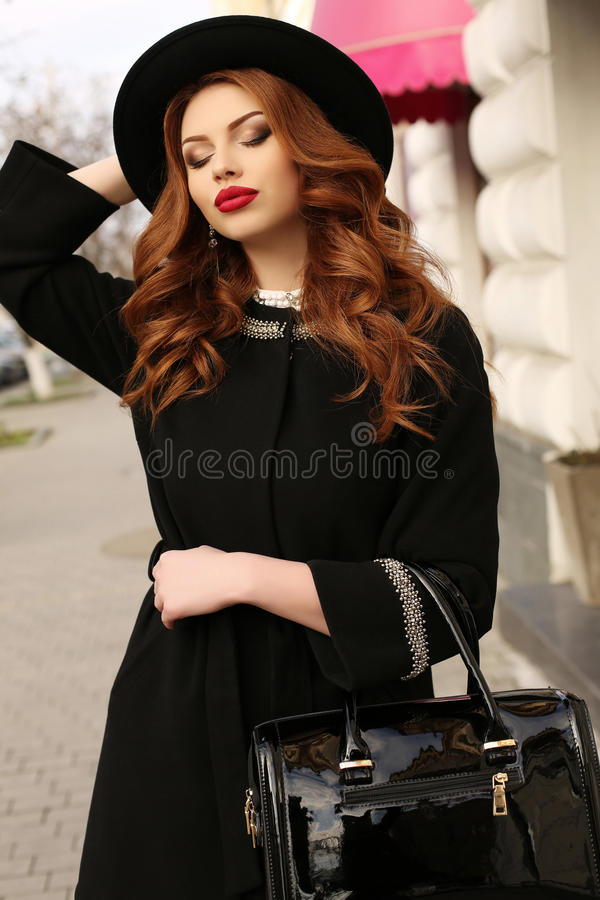 La bella donna con capelli ricci scuri ed il sorriso affascinante, indossa i vestiti eleganti fotografia stock libera da diritti