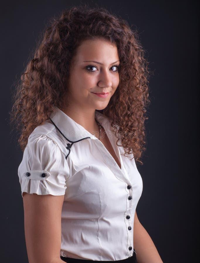La bella donna con casuale compone e capelli ricci fotografia stock