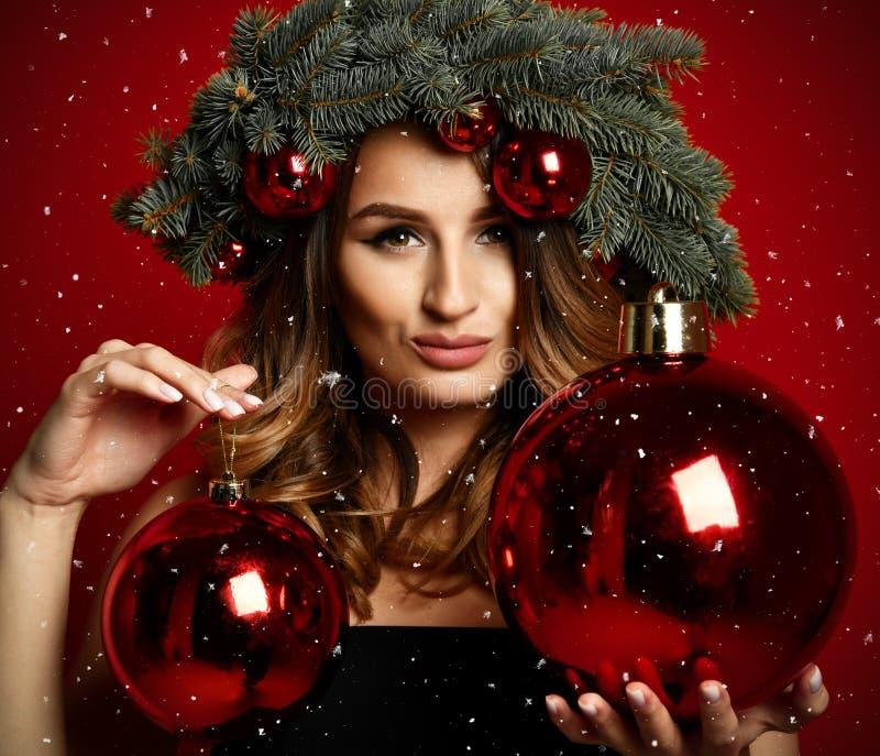 La bella donna con il Natale attilla la corona dell'abete con i coni e le palle rosse della decorazione del nuovo anno fotografie stock