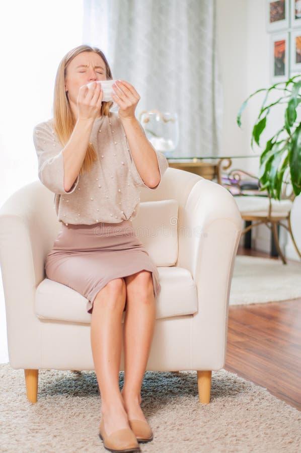 La bella donna con il tovagliolo di carta che starnutisce, avverte i sintomi di allergia immagini stock libere da diritti