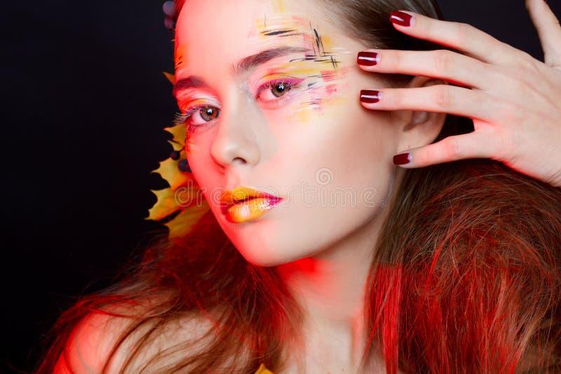 La bella donna con l'autunno compone la posa nello studio modo co immagine stock