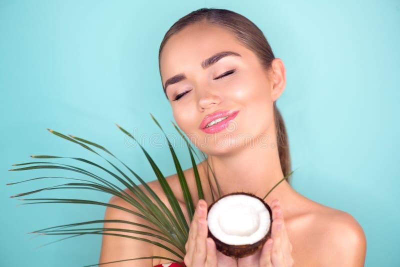 La bella donna con ritratto di cocco Modella Spa con noce di cocco Una giovane faccia da donna brunetta Cura della pelle immagine stock