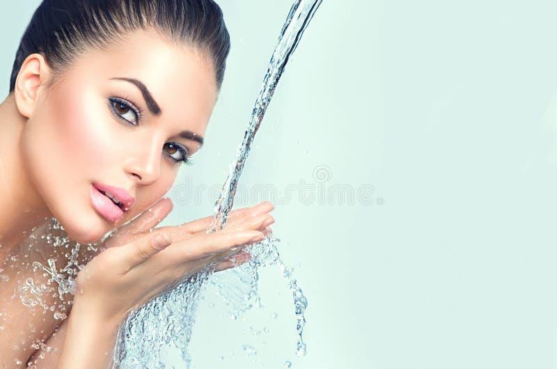 La bella donna con spruzza dell'acqua in sue mani immagine stock libera da diritti