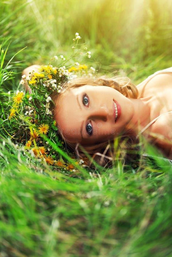 La bella donna in corona dei fiori si trova nell'erba verde fuori fotografia stock libera da diritti