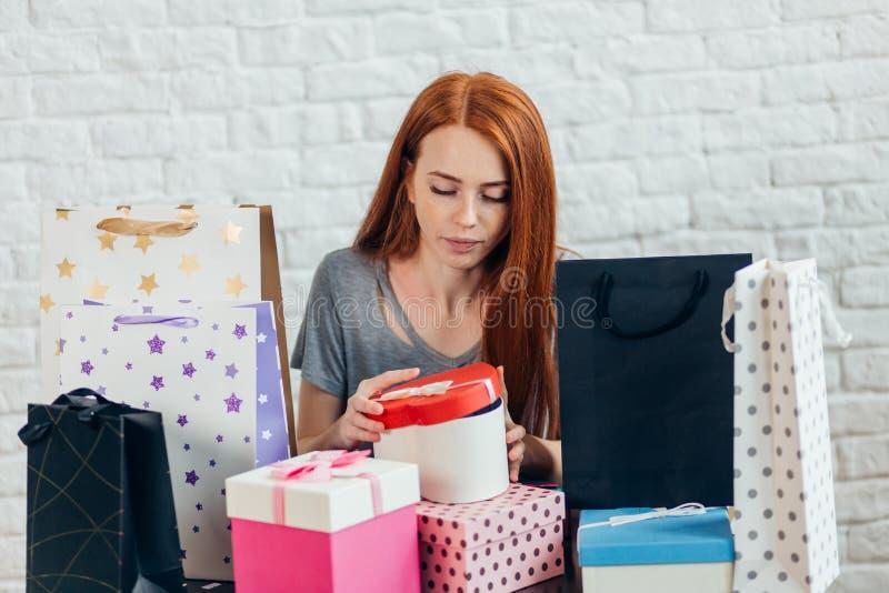La bella donna dai capelli rossi splendida sta aprendo il contenitore di regalo immagini stock