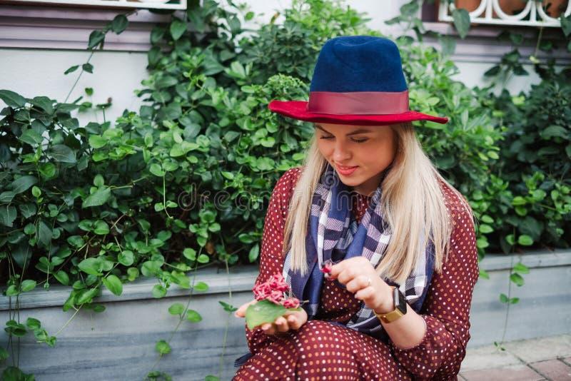 La bella donna dei capelli biondi gode della molla in parco verde immagini stock
