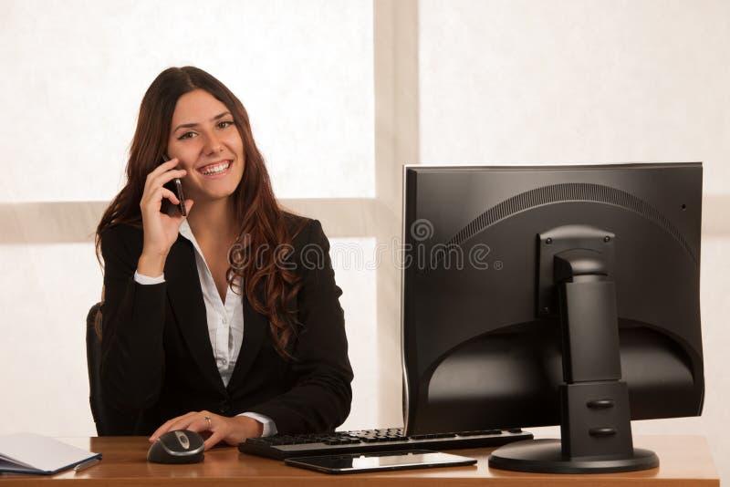 La bella donna di affari parla sullo Smart Phone allo scrittorio in lei fotografia stock