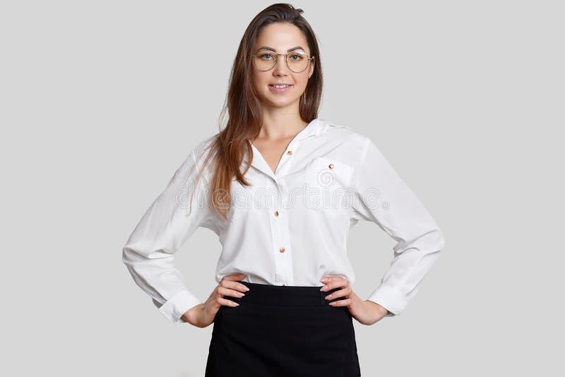 La bella donna di affari sicura tiene le mani sulla vita, porta i vetri rotondi, la blusa bianca e la gonna nera, modelli contro  fotografia stock