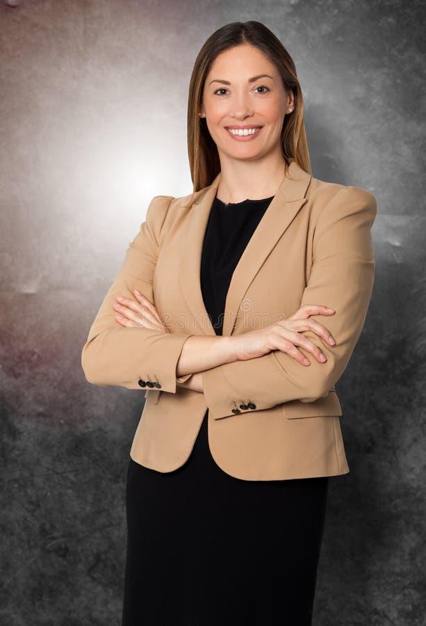La bella donna di affari sorridente arma la condizione piegata fotografie stock