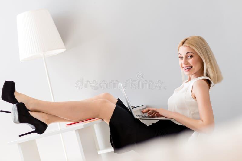 La bella donna di affari sta rilassandosi durante il lavoro immagini stock libere da diritti