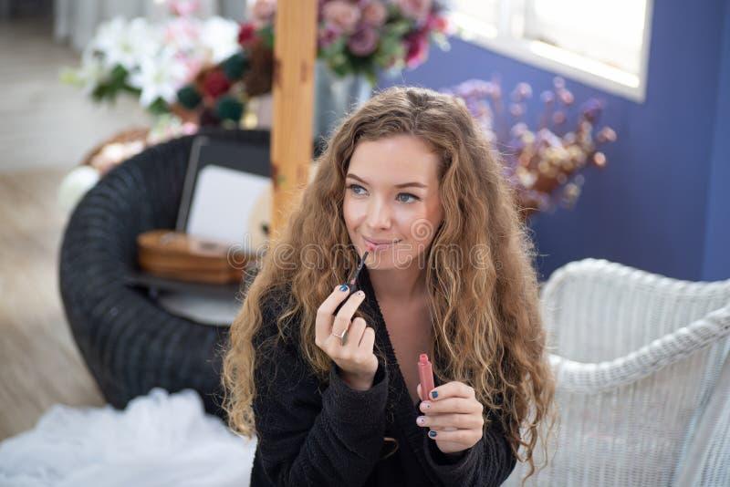 La bella donna dipinge le labbra con rossetto, il modello caucasico dentro compongono ed il concetto del trattamento di bellezza immagine stock libera da diritti