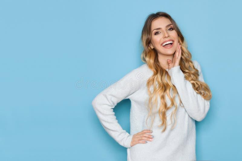 La bella donna divertente in maglione pastello sta tenendo la mano su Chin immagine stock