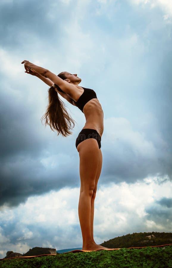 La bella donna esile fa l'esercizio di yoga immagini stock