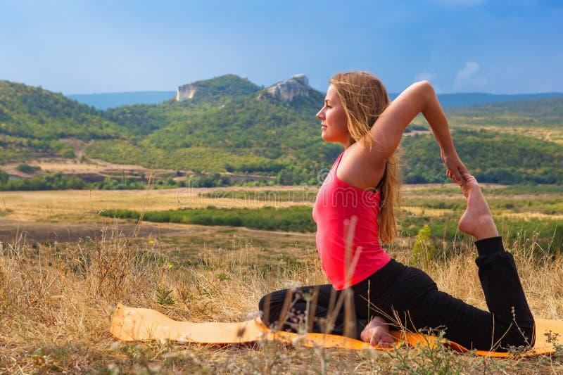 La bella donna esile fa la posa della colomba di yoga fotografia stock