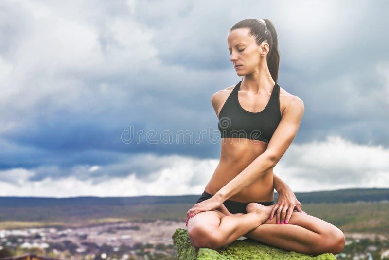 La bella donna esile fa la posa di torsione di yoga fotografia stock libera da diritti