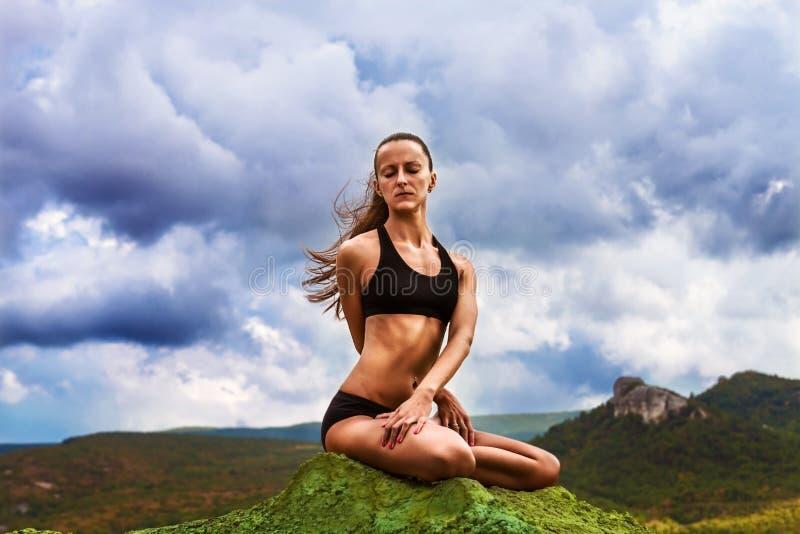 La bella donna esile ha pratica di yoga all'aperto immagini stock