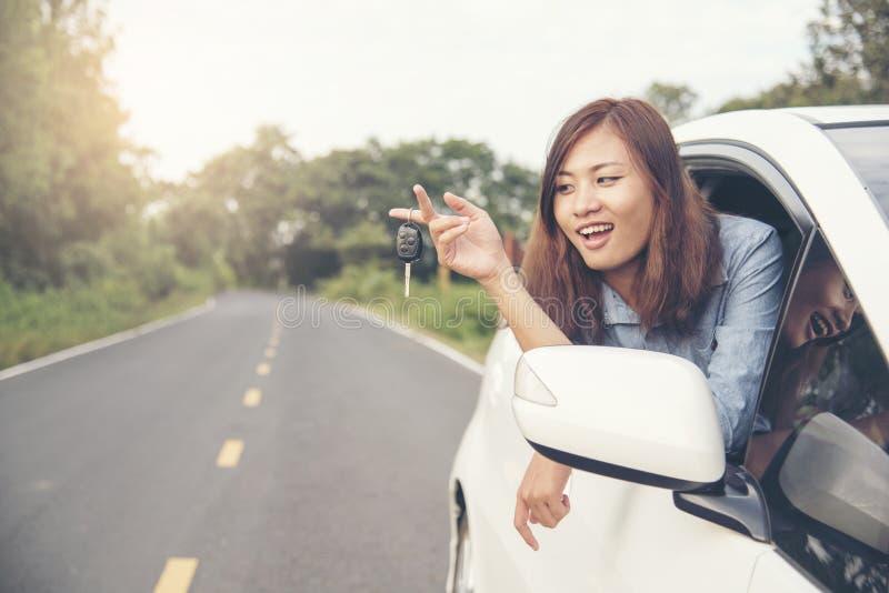 La bella donna ha ottenuto la nuova automobile mostra della chiave dell'automobile dalla finestra dalla nuova automobile fotografie stock