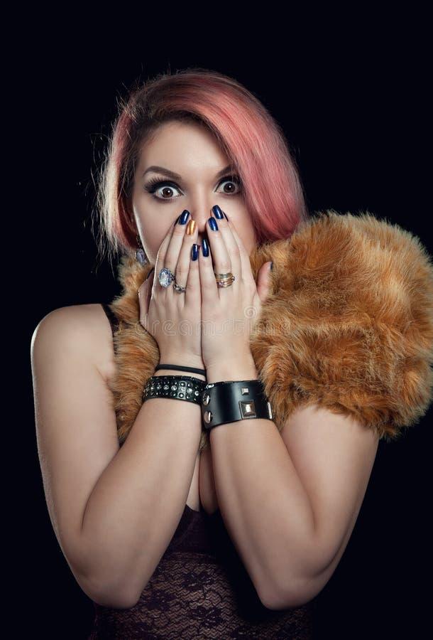 La bella donna ha spaventato la bocca della copertura con le mani immagine stock