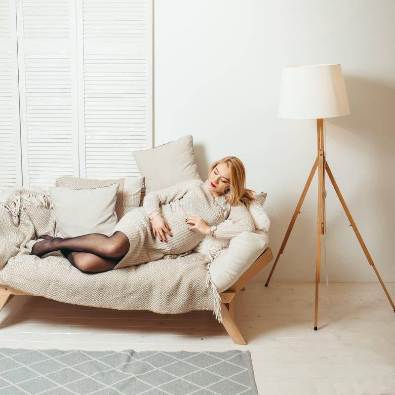 La bella donna incinta bionda con rossetto rosso sta toccando il suo stomaco e sta mettendo sul sofà accogliente nella stanza bia fotografie stock