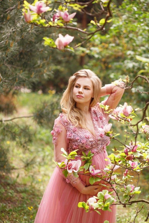 La bella donna incinta in fiori rosa del vestito tocca la pancia della mano che sta vicino all'albero di fioritura della magnolia fotografia stock libera da diritti