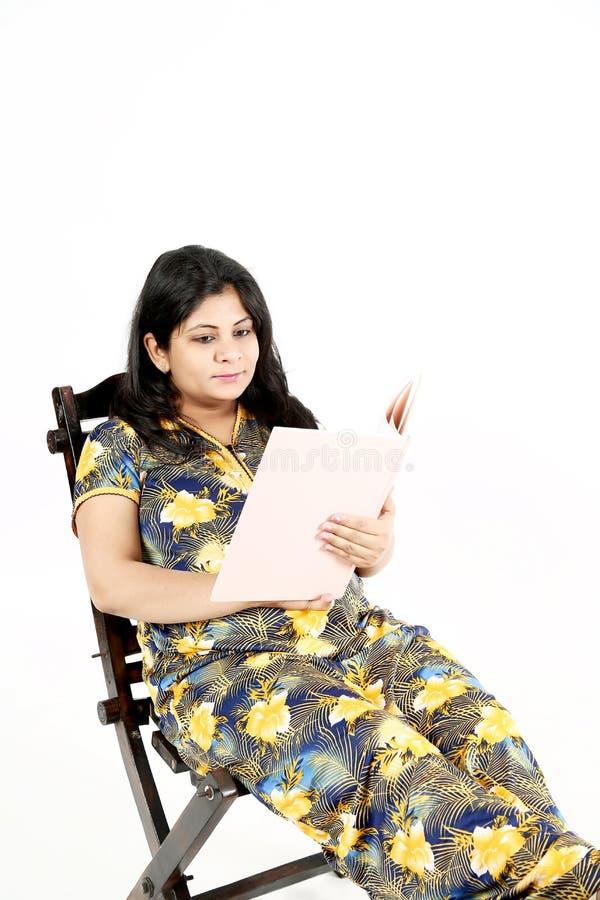 La bella donna incinta sta leggendo la rivista del bambino con la seduta sulla sedia immagini stock libere da diritti