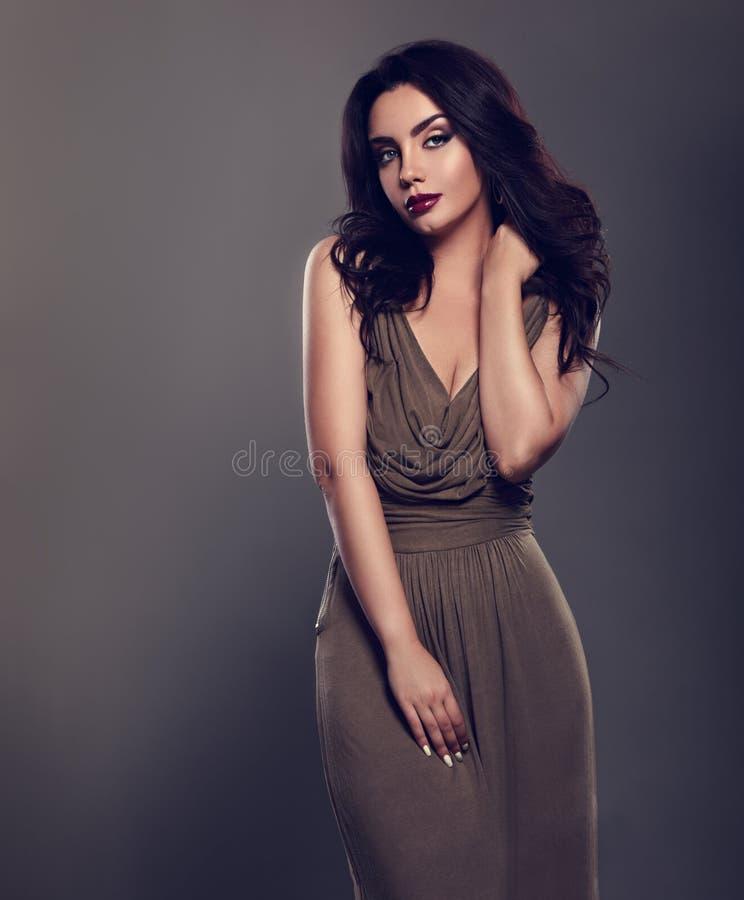 La bella donna intelligente di trucco con stile di capelli ricci nero lungo in vestito elegante verde, rossetto di Borgogna con l fotografia stock
