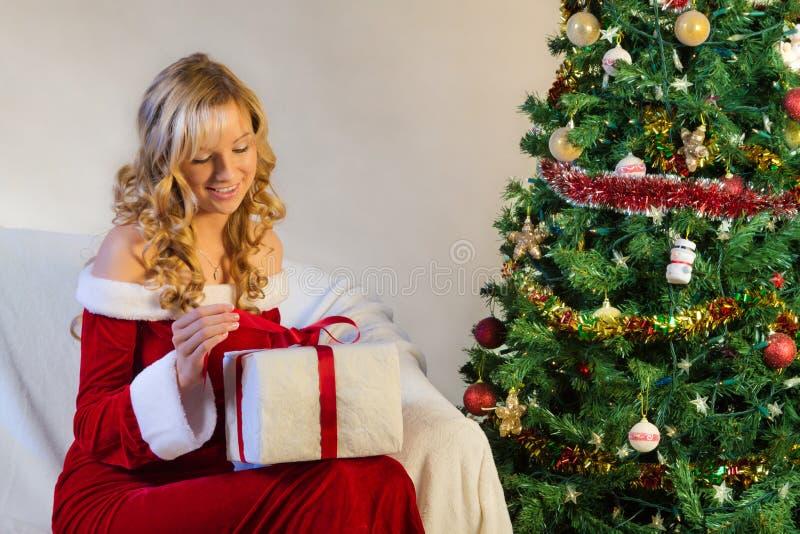 La bella donna nel colore rosso disimballa il regalo di natale immagine stock libera da diritti