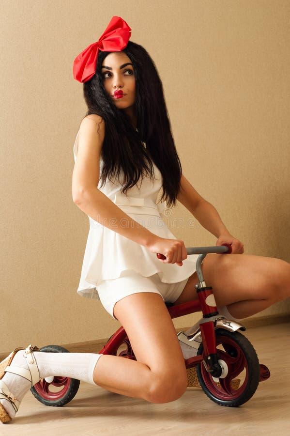 La bella donna nella bambola di immagine sta sedendosi sulla piccola bicicletta immagini stock libere da diritti
