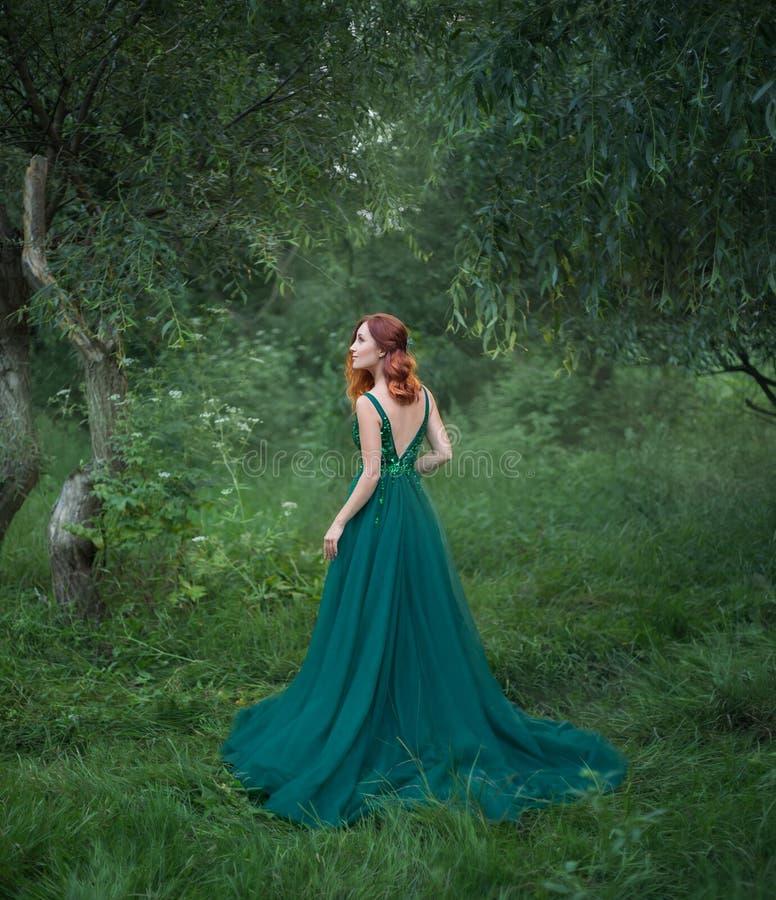 La bella donna nella foresta sta stando con lei di nuovo alla macchina fotografica fotografia stock